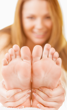 Close-up woman applying moisturizer cosmetic cream on foot on light background. Focus on feet