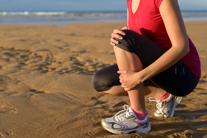 Female runner clutching her shin because of a running injury and inflammation. Tibial periostitis hurt while jogging on beach.