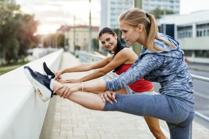 Two women stretching feet before jogging